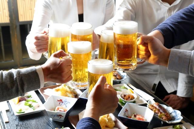 おつまみの乗ったテーブルの上でビールで乾杯する人々