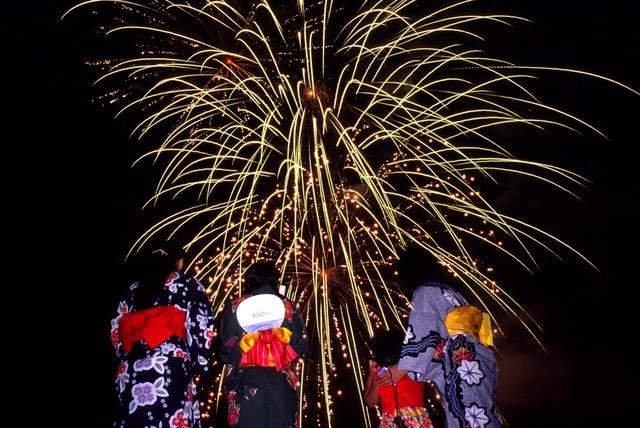 夜空に打ち上がる大輪の花火とそれを眺める浴衣の女性達と子供