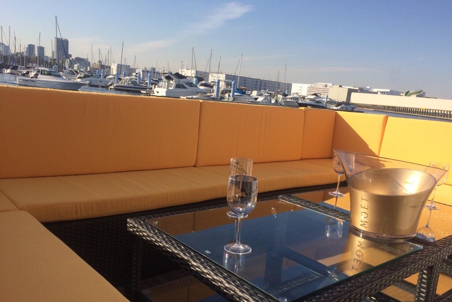 黄色いソファーに囲まれたミッドブルー号の後方デッキと中央のテーブルに置かれたシャンパングラス