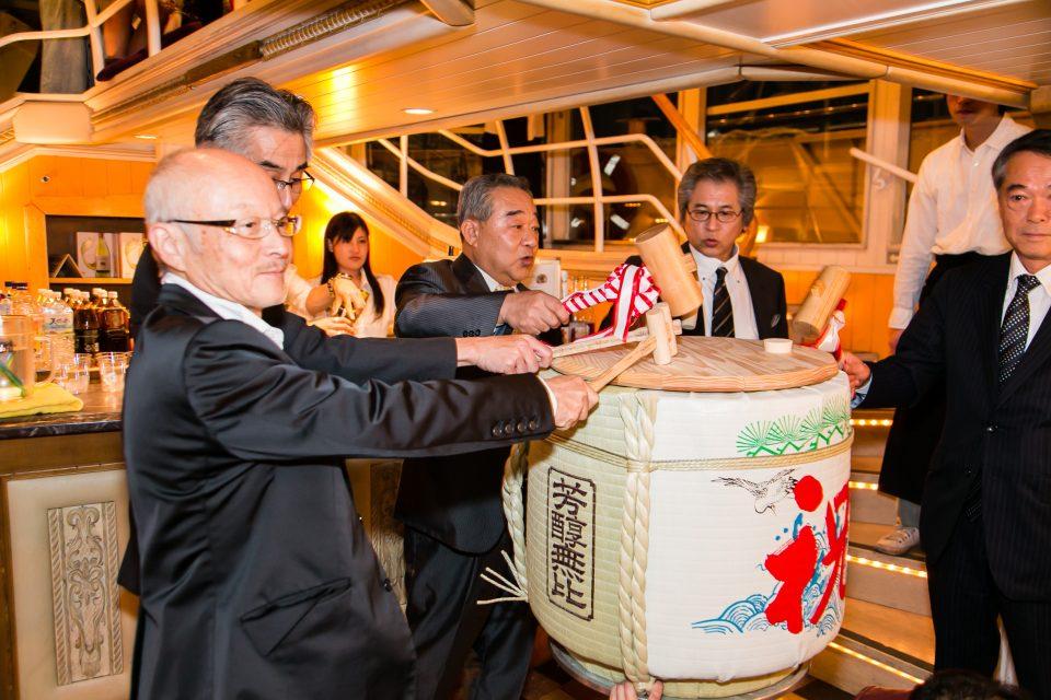 洋風屋形船の船内で樽酒の鏡割りを行う貫禄のあるスーツの男性5人