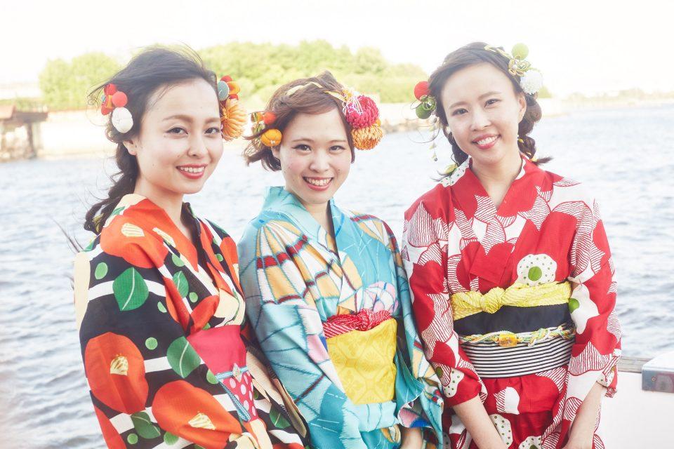 お台場をバックにアニー号のデッキでポーズを取る浴衣を着た3人の若い女性たち