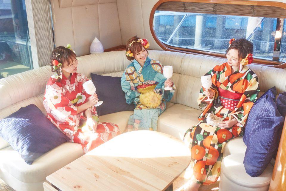 ミッドブルー号の船内でシャンパンを楽しむ浴衣を着た若い3人の女性たち