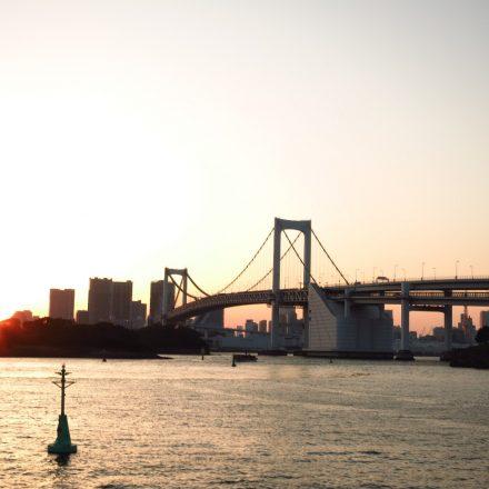 東京湾から見た夕暮れ時の街とレインボーブリッジ