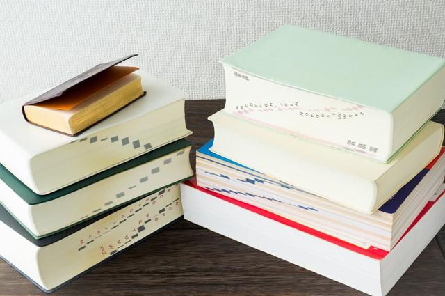 卓上に積み上がるさまざまな辞書