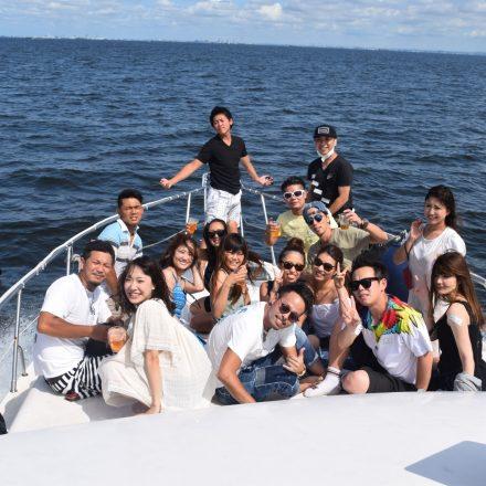 ミッドブルー号の前方デッキで大海原をバックに記念撮影する20名程の若い男女