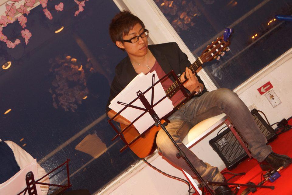 桜で装飾されたステージで演奏するギタリスト