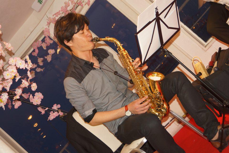 桜で装飾されたステージでサックスを吹くミュージシャン