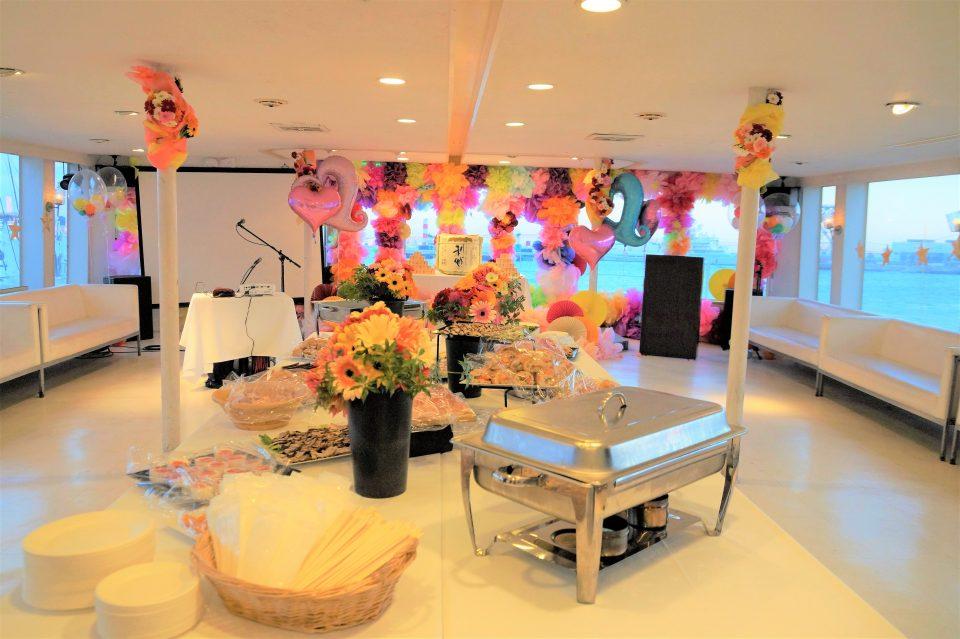 ビュッフェ台に並んだビュッフェ料理とバルーンや装花で華やかに装飾されたセレブリティ2号の船内
