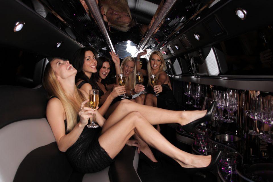 リムジンの車内でシャンパンを持って乾杯する女性達