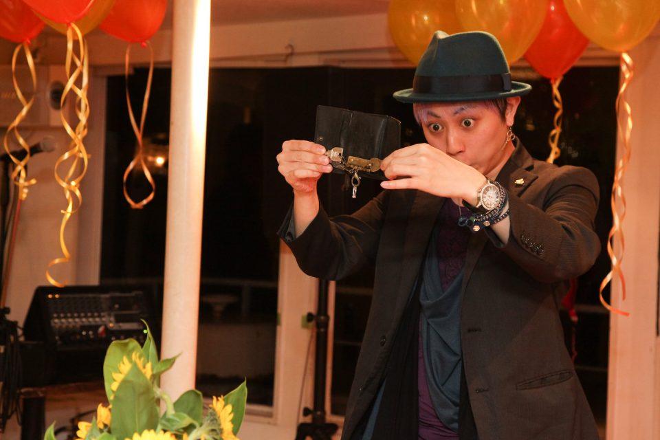 洋風屋形船の船内で鍵を使ったマジックを披露する若い男性マジシャン