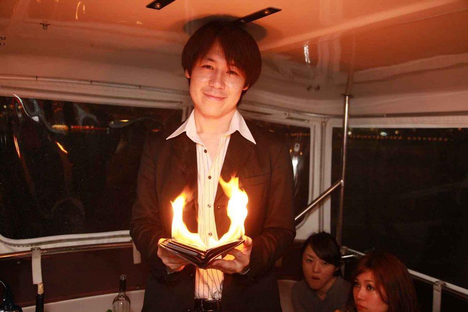 洋風屋形船の船内で炎を使ったマジックを披露する男性マジシャン