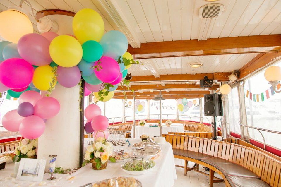 バルーン装飾とテーブルクロスで飾られた洋風屋形船の船内とビュッフェ料理