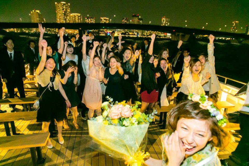 洋風屋形船の屋上デッキでブーケトスを行おうとしている新婦とブーケを待ちわびる若い女性たち
