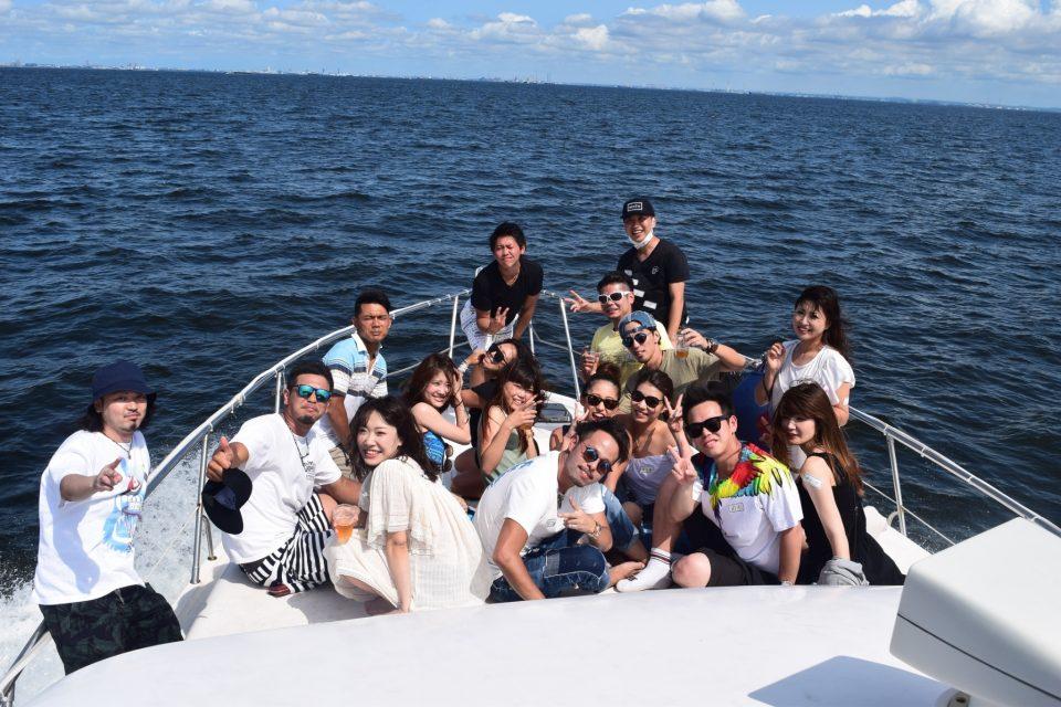 ミッドブルー号の前方デッキで大海原をバックに集合写真を撮る20名程の男女
