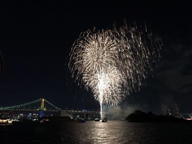 船上から眺める打ち上げ花火とライトアップされたレインボーブリッジ