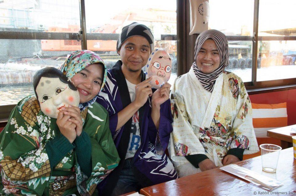 屋形船の船内で着物を着て仮面を持ち嬉しそうに記念撮影する3名の外国人