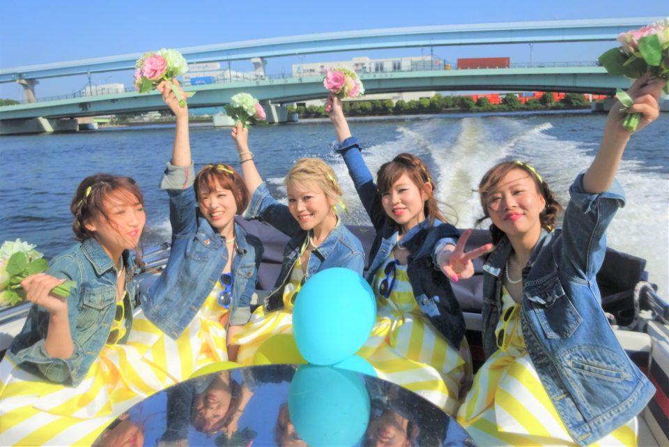 東京湾を疾走するアニー号のデッキでポーズを取る若い女性たち