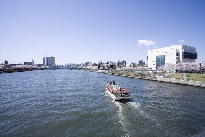 晴天の中河川上を走る屋形船
