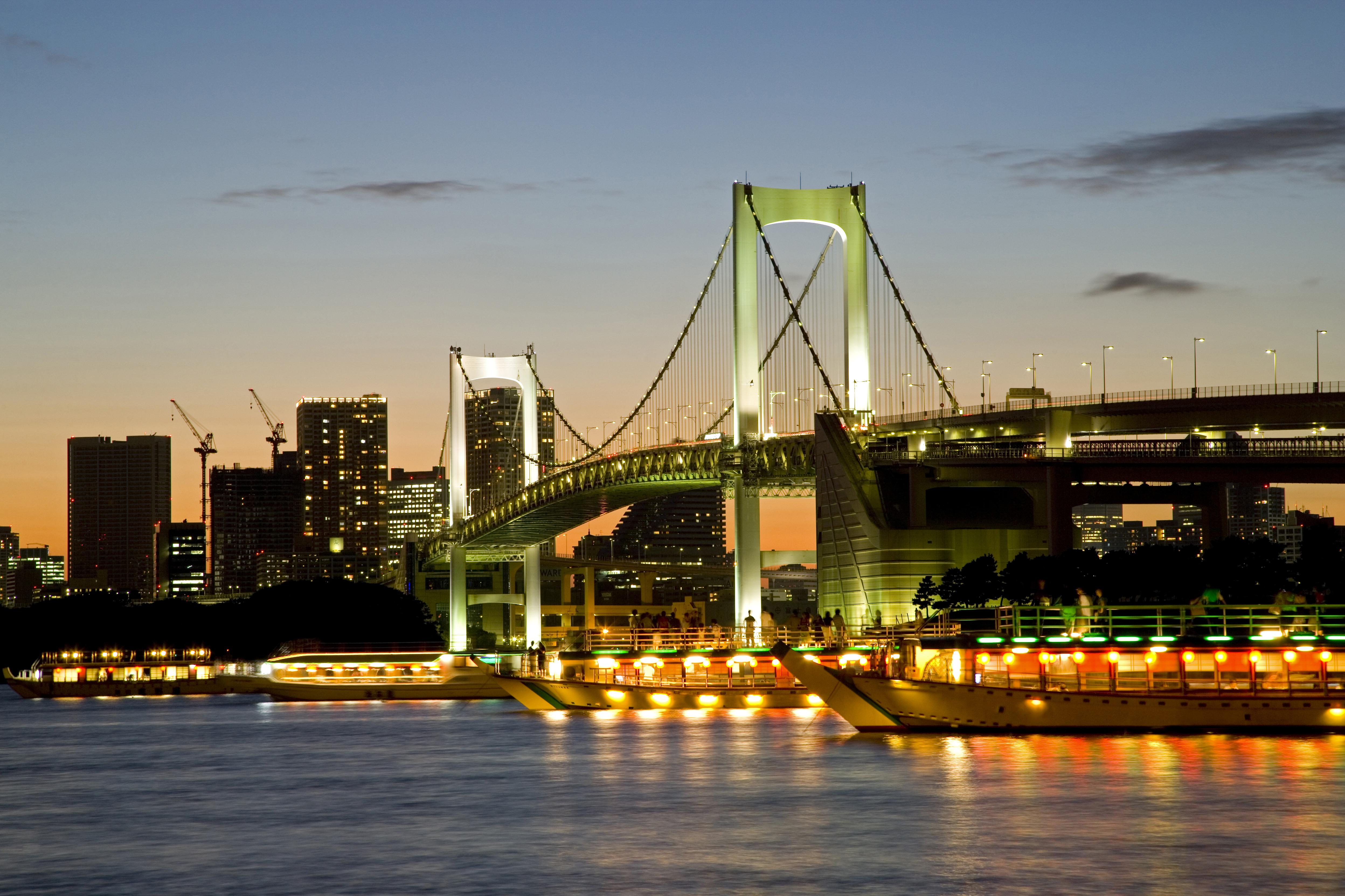 レインボーブリッジの夜景と東京湾に浮かぶたくさんの屋形船