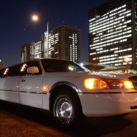 夜のビル街に停まった白いリムジン