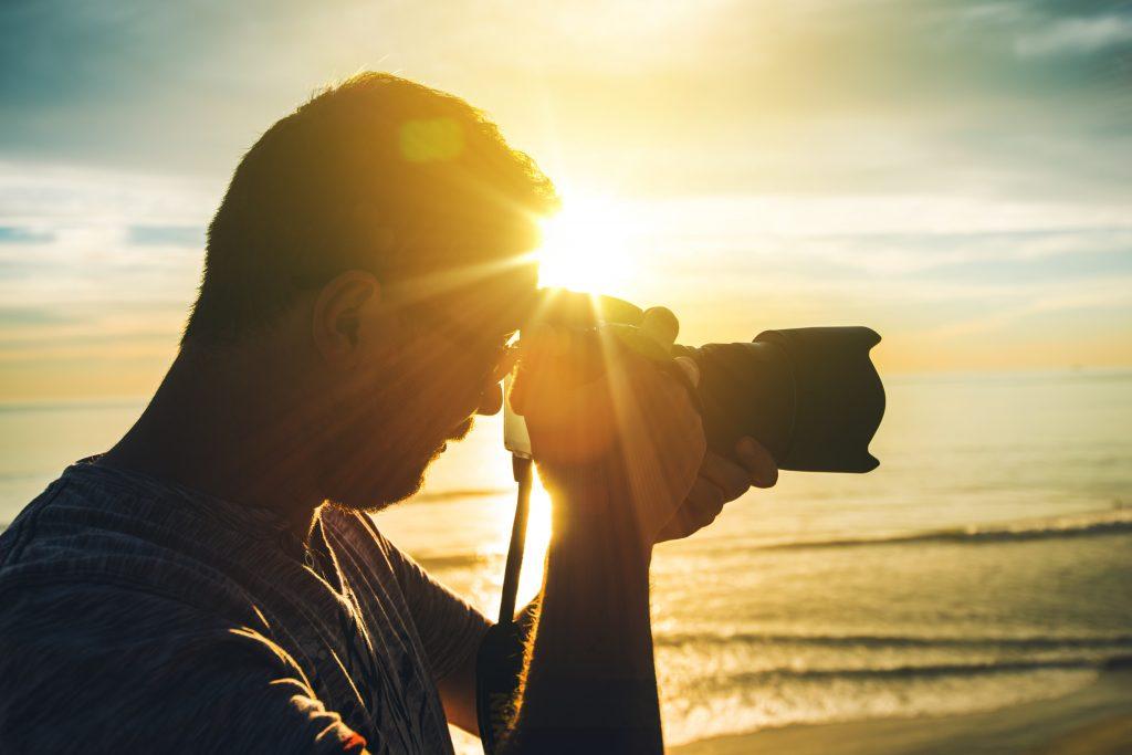 海岸で夕日をバックに一眼レフカメラを構えるプロカメラマン