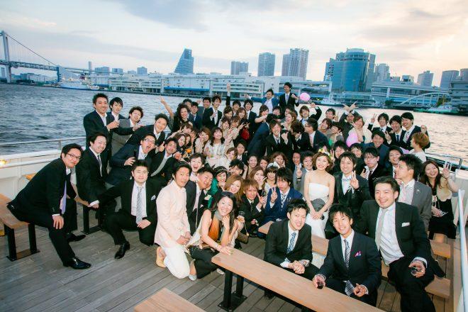 洋風屋形船の屋上デッキで東京湾をバックに結婚式二次会の記念撮影をする70名程のお客様