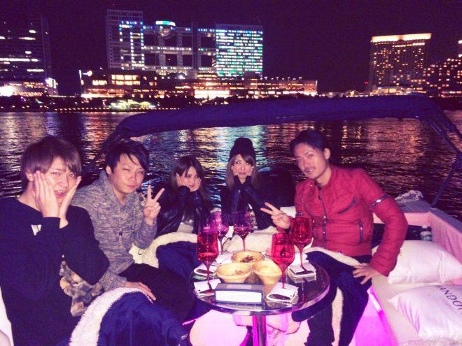 お台場の湾上に浮かぶ船でパーティーをしている男女のグループ