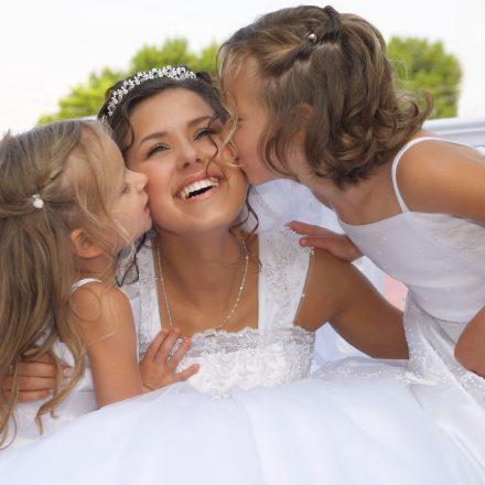 ウェディングドレスを着た女性に女の子が左右からキスしている風景