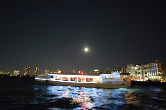 お台場の湾上から眺める月とライトアップされた屋形船