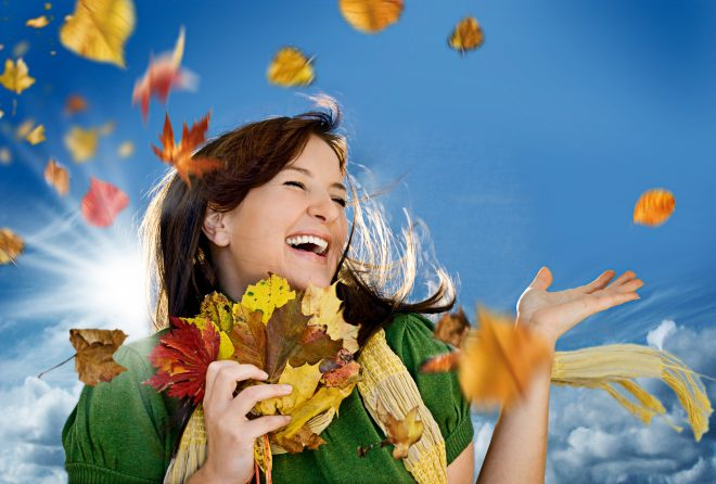 笑顔の外国人女性とさまざまな木の葉っぱが舞う景色