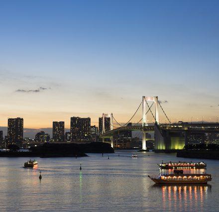俯瞰視点で眺めるライトアップされたレインボーブリッジと湾上に浮かぶ屋形船