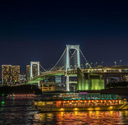 幻想的にライトアップされたレインボーブリッジと屋形船