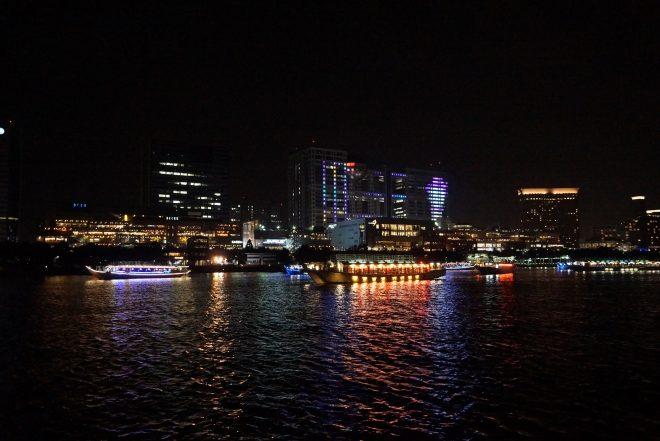 水上に浮かぶライトアップされた屋形船とお台場の夜景