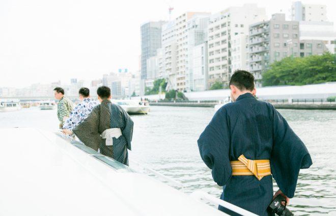 浴衣で川沿いを歩く男性たち