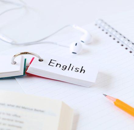 机に置かれた辞書とノートと単語帳と鉛筆とイヤホン