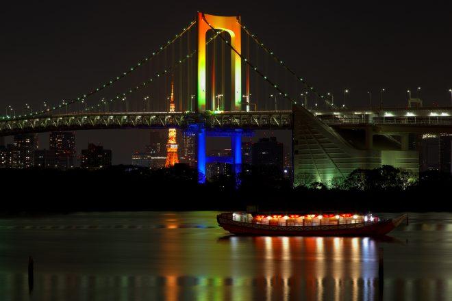 夜のレインボーブリッジと湾に浮かぶ屋形船
