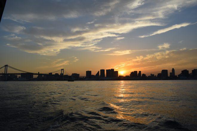 船上から眺める街に沈みゆく夕日