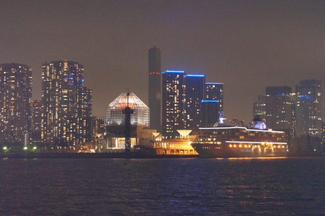 船上から眺める巨大船が停泊する港街の夜景