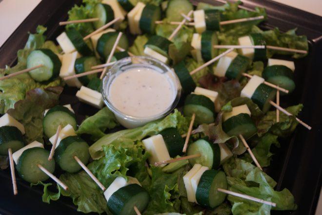 レタスの上に爪楊枝でまとめられたきゅうりとチーズのサラダ
