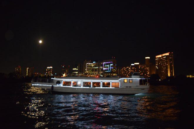 街の夜景と水上に浮かぶライトアップされた屋形船