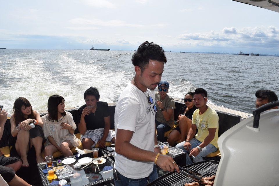 ミッドブルー号の後方デッキで本格BBQグリルを使った船上バーベキューを楽しむ若い男女