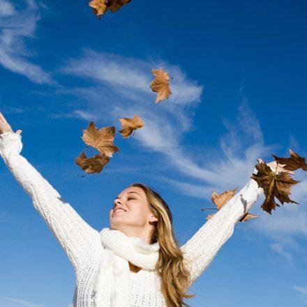 青空のもと両手を掲げて風を感じている外国人女性