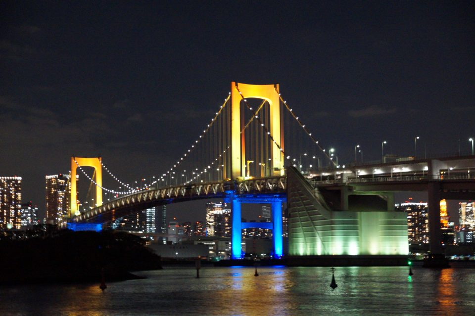 東京湾の夜景と虹色にライトアップされたレインボーブリッジ
