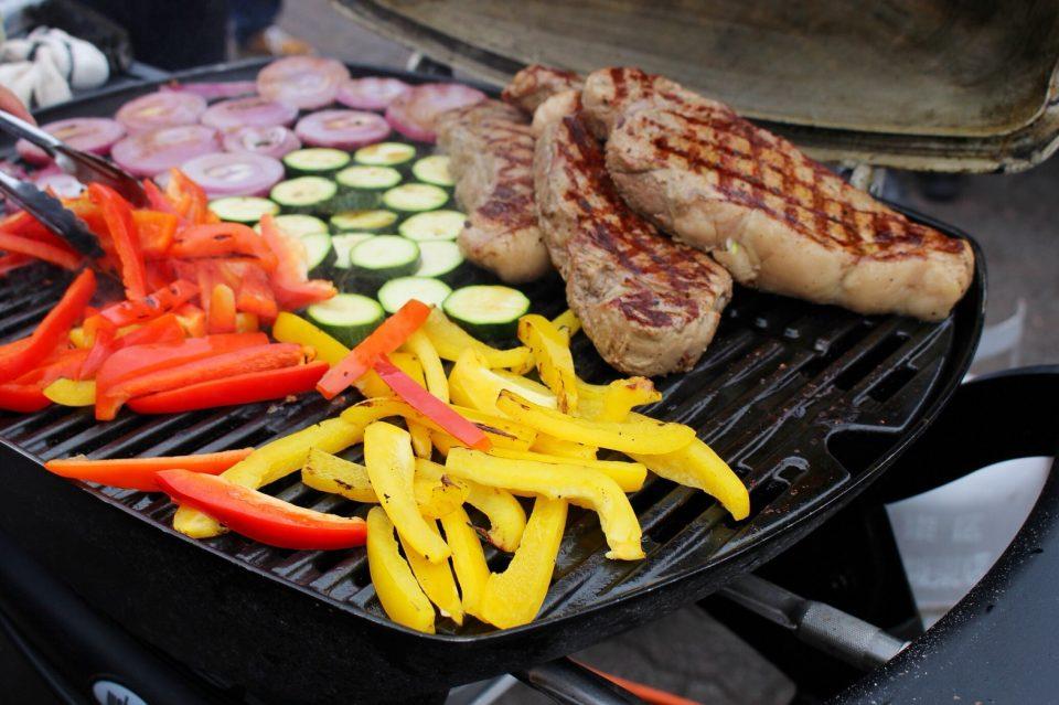 本格BBQグリルで焼かれるステーキと色とりどりの野菜