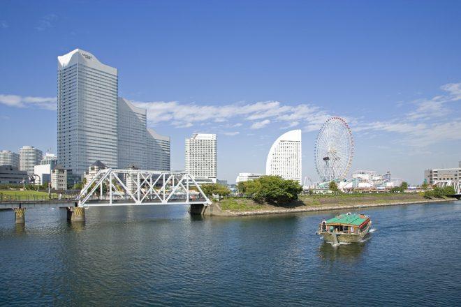 横浜の運河を航行する屋形船の背景に見えるコスモクロック21やインターコンチネンタルホテル