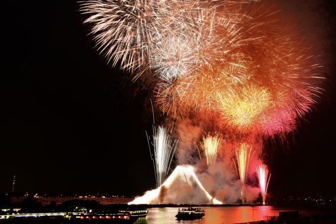 夜空に大きく打ち上げられた花火と多数の屋形船