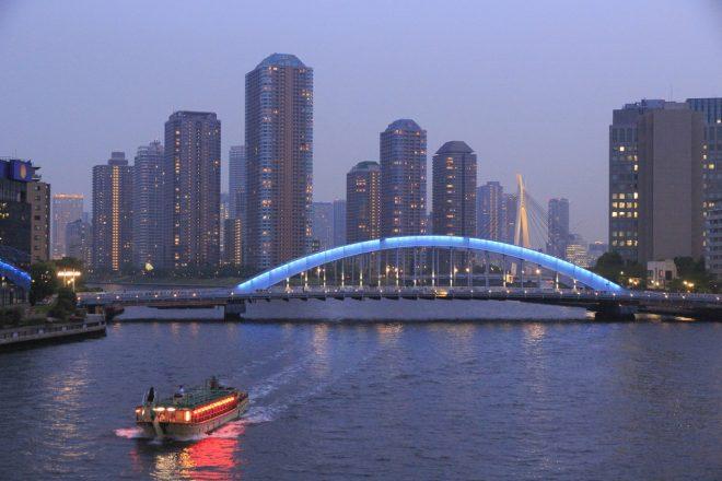 隅田川に架かる永代橋とその下を潜る屋形船
