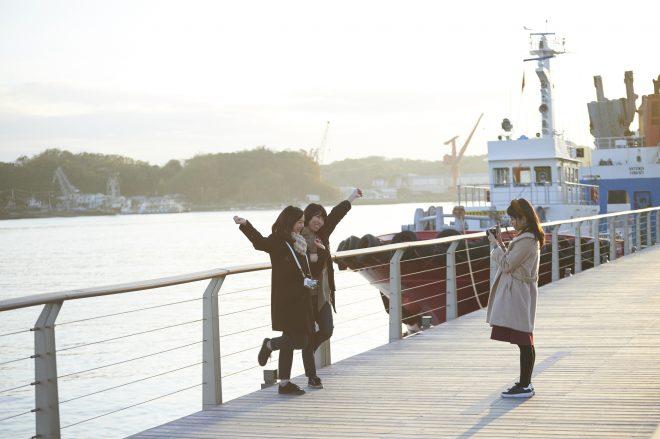 港をバックに写真撮影している女性3人