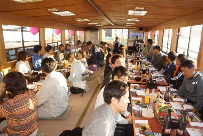 屋形船で料理を囲んでくつろぐ人たち