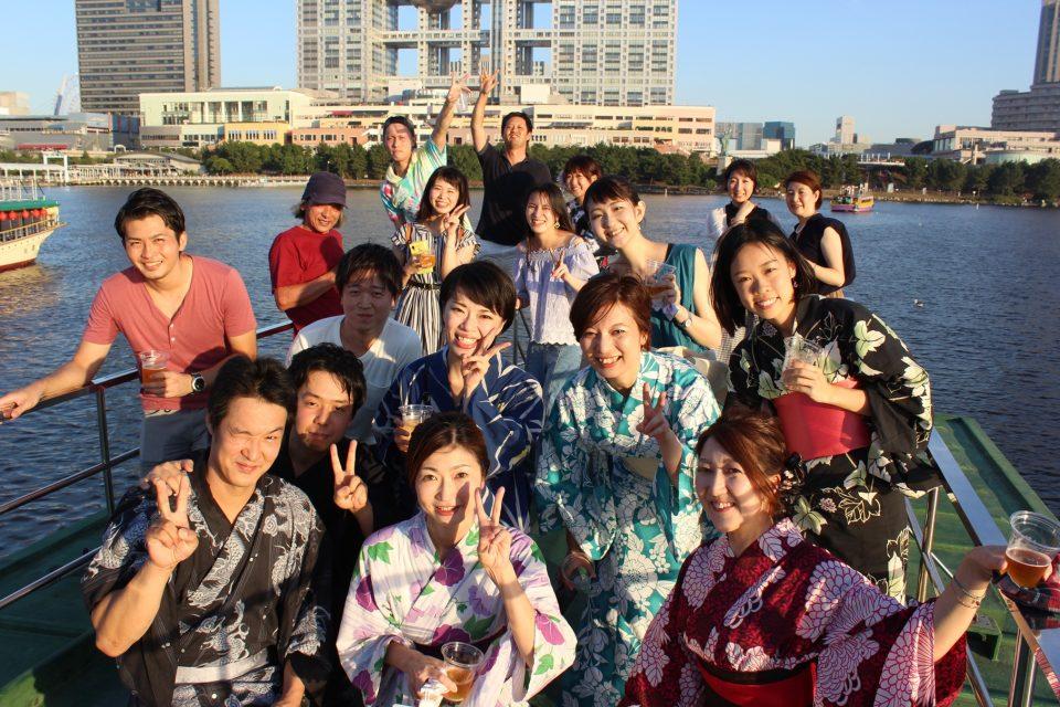 屋形船の屋上デッキで夕焼けのお台場をバックに笑顔で集合写真を撮る20名程の男女